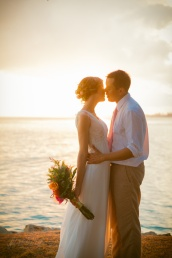 The bride and groom share a kiss at sunset