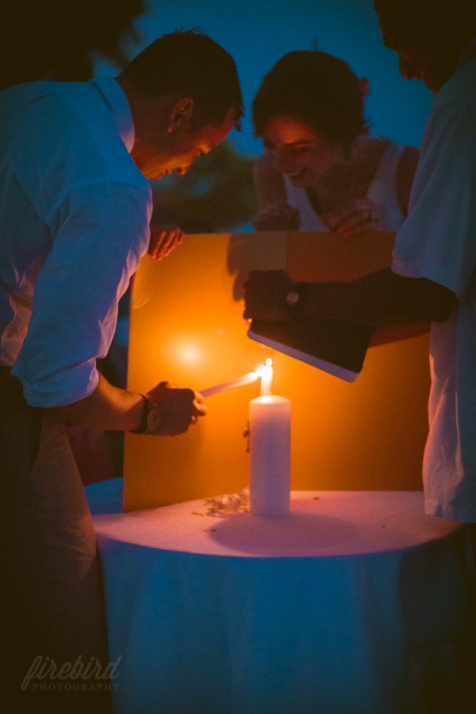 the bride and groom light a ceremonial candle